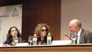 Emma Mayo en la mesa de ponentes, charlando con el presidente de ConArtritis